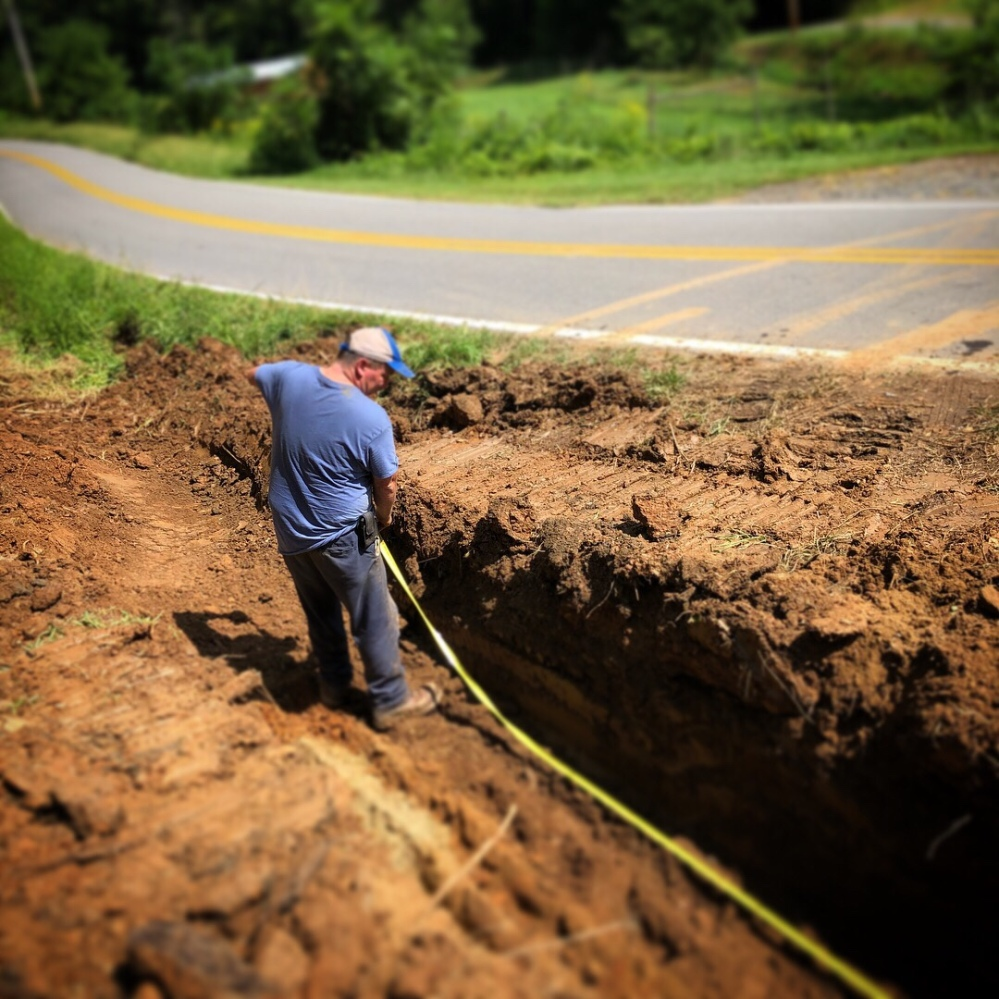 Sam measuring for drainage pipe down near paved road